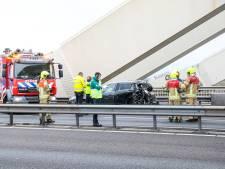 Vrachtwagen knalt op stilgevallen auto op Van Brienenoordbrug: twee inzittenden gewond