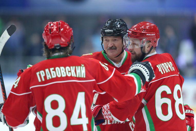 De Wit-Russische president Aleksandr Loekasjenko (midden) deed afgelopen weekend gewoon mee aan een ijshockey-wedstrijd. Beeld via REUTERS