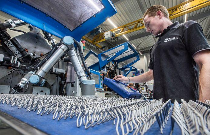 Medewerker Willem controleert de robot die producten maakt voor vloerverwarmingsleidingen.