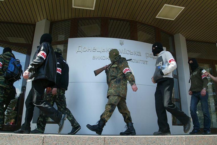 Gewapende mannen voor een overheidsgebouw in Donetsk vandaag. Beeld AP