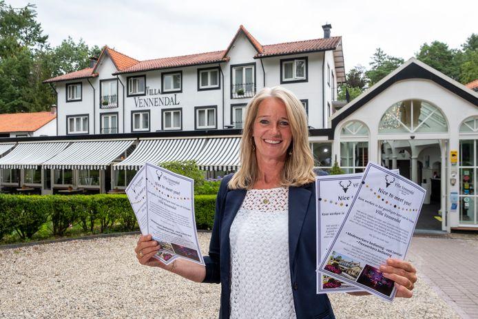 Eigenaresse Frederique van der Vleuten-Jung met folders die in Nunspeet huis-aan-huis verspreid werden om personeel te werven voor Hotel Villa Vennendal.