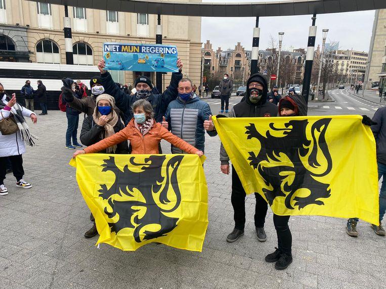 Sommige actievoerders hebben Vlaamse vlaggen en pancartes van een eerdere betoging van Vlaams Belang bij. Beeld Dieter Nijs