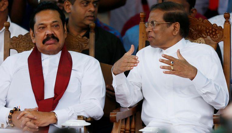 De nieuw aangestelde premier van Sri Lanka Rajapaksa en president Sirisena overleggen tijdens een protestbijeenkomst vlak bij het parlement in Colombo. Beeld Reuters