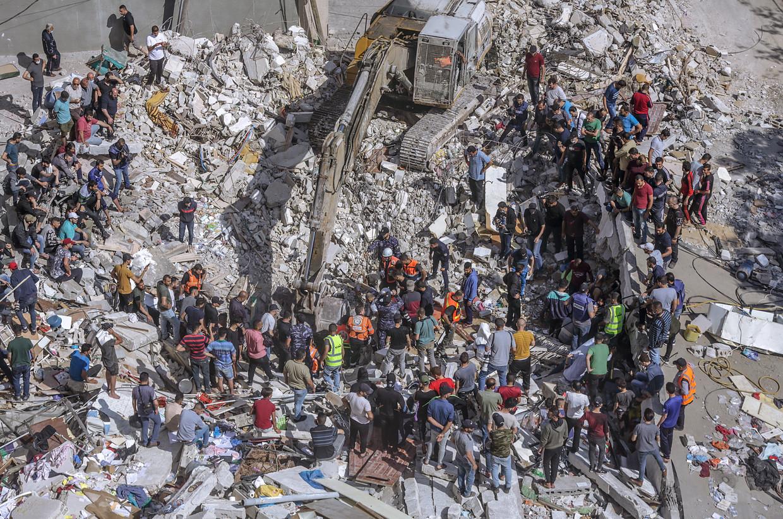 Palestijnse hulpdiensten zoeken naar overlevenden in het puin van een gebombardeerd pand in Gaza-Stad. Beeld EPA