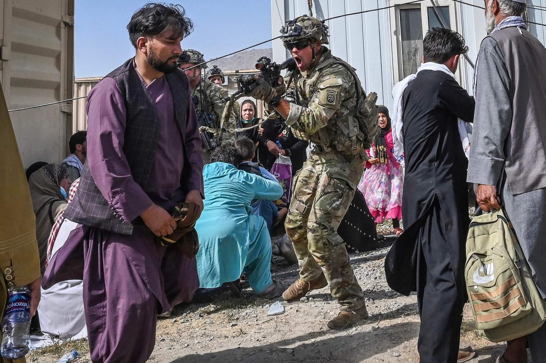 Een VS-soldaat richt zijn geweer op Afghaanse burgers die trachtten weg te vluchten, op de luchthaven van Kaboel. Beeld AFP