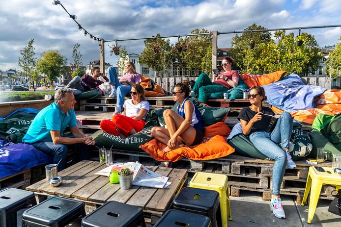 Mensen genieten van het mooie weer op het terras van ROOST aan de Singel.