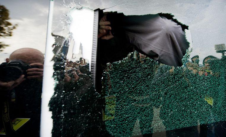 Een lid van English Defence League bedekt zijn gezicht terwijl hij wegrijdt in een vernield busje. Foto © Koen van Weel/anp<br /> Beeld