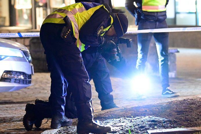 Politieagenten onderzoeken sporen na de aanval.