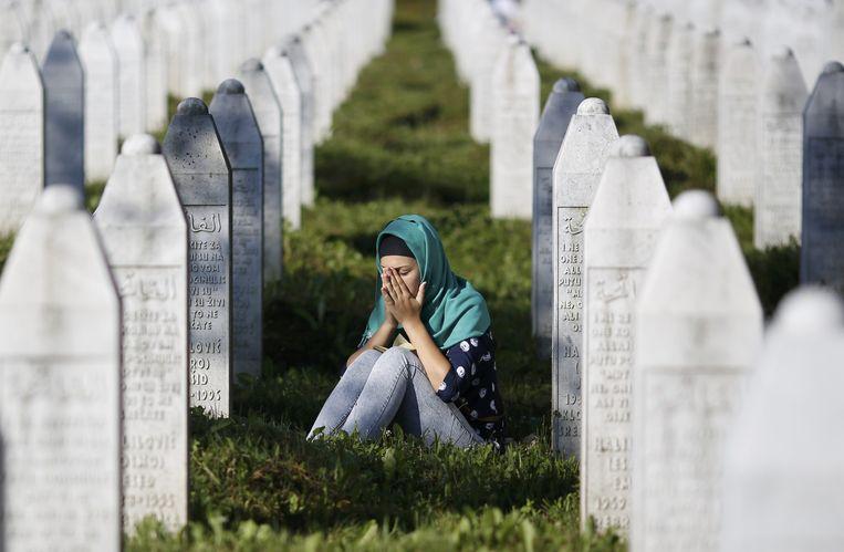 Een jonge vrouw rouwt tussen de graven van de begraafplaats bij Potocari. Toen de premier deze begraafplaats wilde betreden werd hij dus bekogeld met stenen. Beeld REUTERS