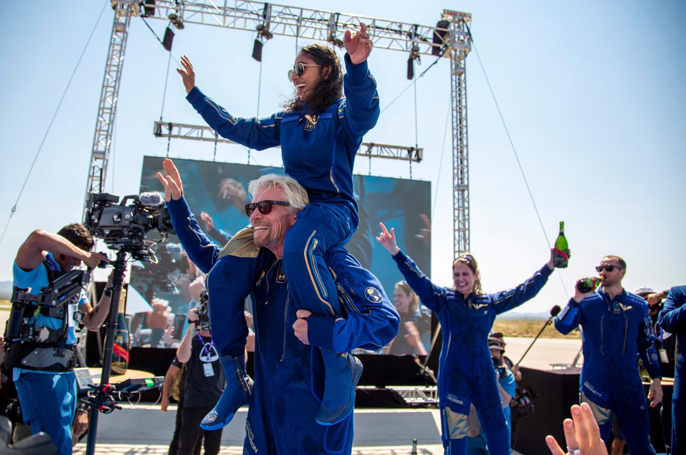 Euforisch viert Richard Branson met medebemanningslid Sirisha Bandla op zijn nek de terugkeer na hun eerste ruimtevlucht.
