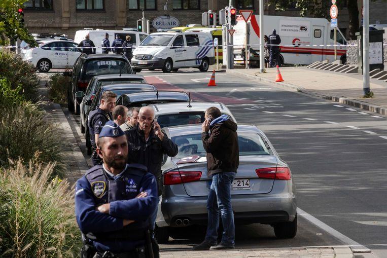 Politiemensen onderzoeken de plek in Schaarbeek waar drie van hun collega's werden verwond. Beeld AP