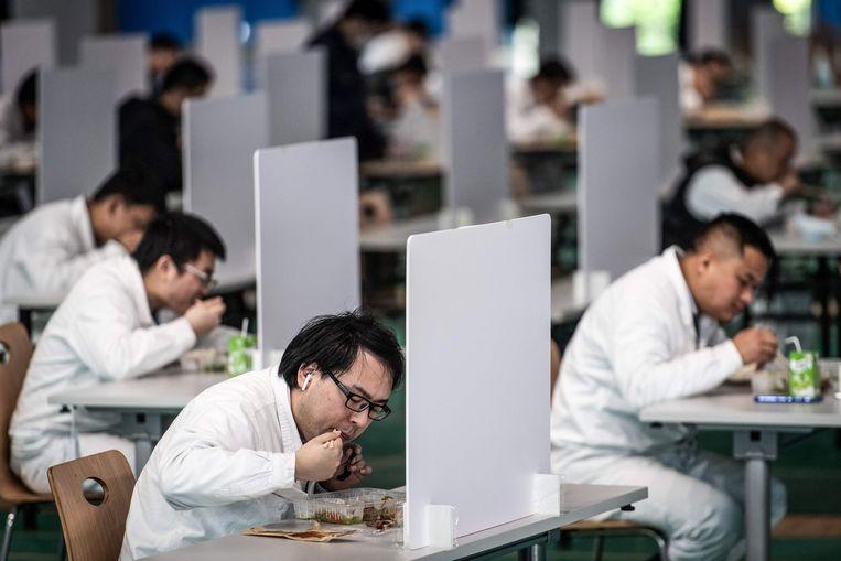 Werknemers in Wuhan eten sinds de heropstart van fabrieken veilig apart.  Beeld AFP