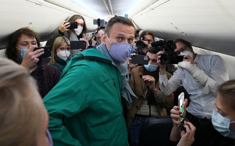 Aleksej Navalny, omringd door journalisten in het vliegtuig waarmee hij opsteeg op de luchthaven Berlijn Brandenburg.   Beeld AP