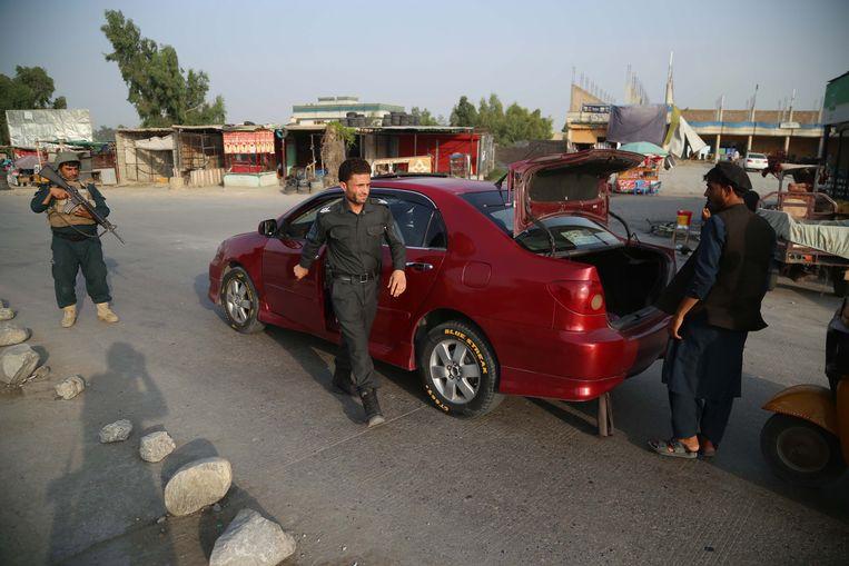 Afghaanse veiligheidsfunctionarissen bewaken een controlepost in de stad Jalalabad in het oosten van het land. Beeld EPA