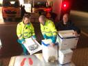 Medewerkers van de ambulancepost nemen de ingezamelde spullen in ontvangst.