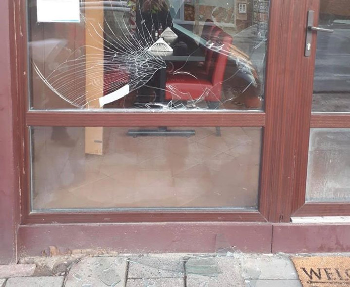 Een kapotte ruit bij een restaurant, ontstaan door de worsteling met de politie.