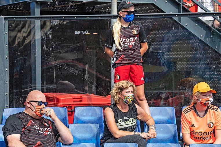 Een familie van Feyenoordsupporters heeft zich beschermd tegen hitte en corona.  Beeld Guus Dubbelman / de Volkskrant