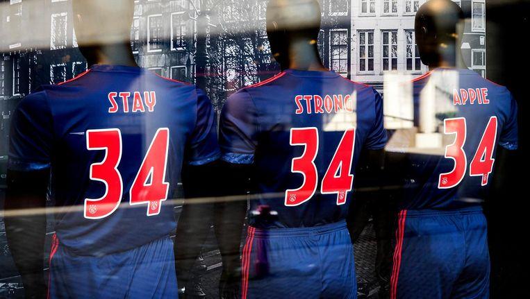 In de etalage van de fanshop van Ajax staan drie clubshirts die samen de tekst Stay Strong Appie laten zien Beeld anp