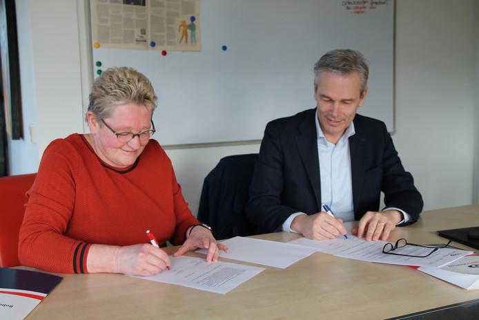Bestuurders Monique Beukers (Robert Coppes stichting) en Tom van Mierlo (Reinier van Arkel) bekrachtigen de samenwerking door het tekenen van een convenant.