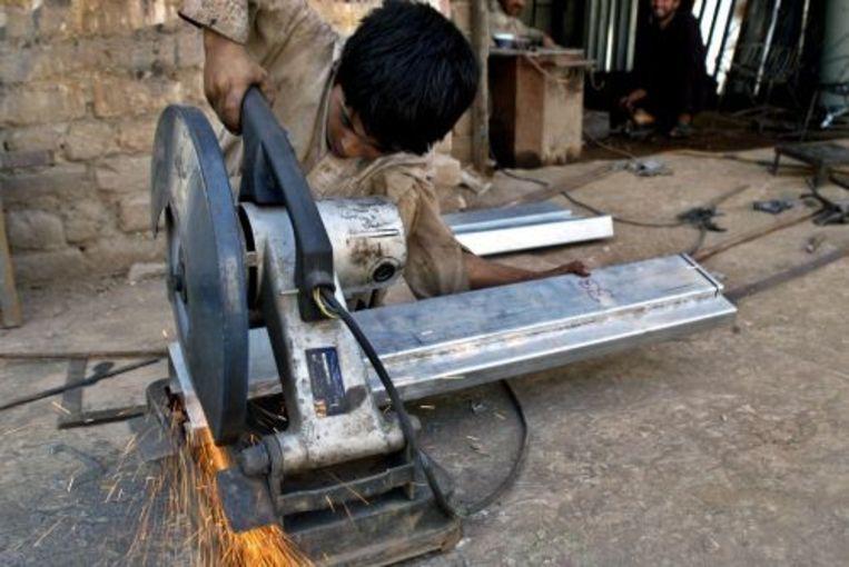 Een Pakistaanse jongen snijdt ijzer op straat. Zaterdag vindt VN-Werelddag tegen Kinderarbeid plaats. ANP Beeld