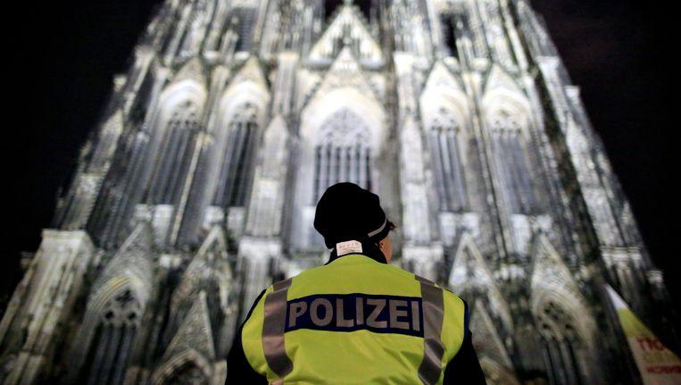 Een politieagent vlak voor de kathedraal in Keulen. Beeld EPA