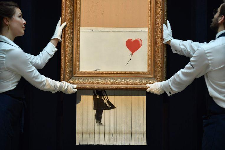 Sotheby's-personeelsleden poseren met het 'nieuwe' kunstwerk van Banksy, dat hij 'Love Is in the Bin' doopte, nadat het oorspronkelijke werk 'Girl with Balloon' tijdens een kunstveiling plots voor de helft uit de lijst schoof en er versnipperd weer uitkwam.  Beeld AFP