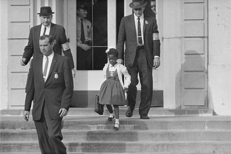 Enkele federale agenten escorteren een zesjarige Ruby Bridges naar school in 1960. Beeld AP
