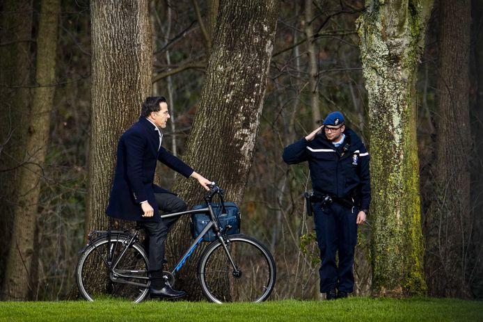 Een marechaussee salueert terwijl premier Mark Rutte op de fiets aankomt bij het Catshuis, voor het eerste kabinetsberaad over de affaire rond de kinderopvangtoeslag op de ambtswoning van de premier.