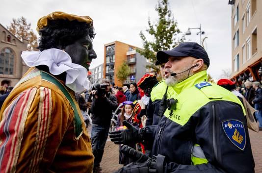 Edwin Wagensveld (l), voorman van Pegida, wordt verkleed als Zwarte Piet aangehouden in Apeldoorn tijdens de intocht van Sinterklaas.