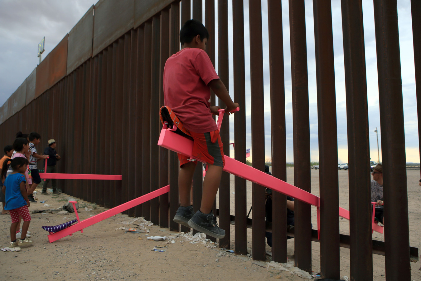 Amerikaanse en Mexicaanse families spelen op een wip die tussen de spijlen van een grenshek is bevestigd.