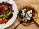 Een galette (uientaartje) met vijgen en geitenkaas, met daarnaast een groene salade met biet en gefermenteerde reepjes wortel.