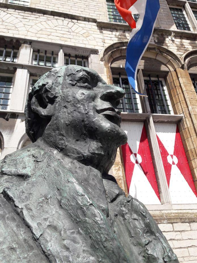 Anton van Duinkerken tegen de achtergrond van het stadhuis op de Grote Markt van Bergen op Zoom