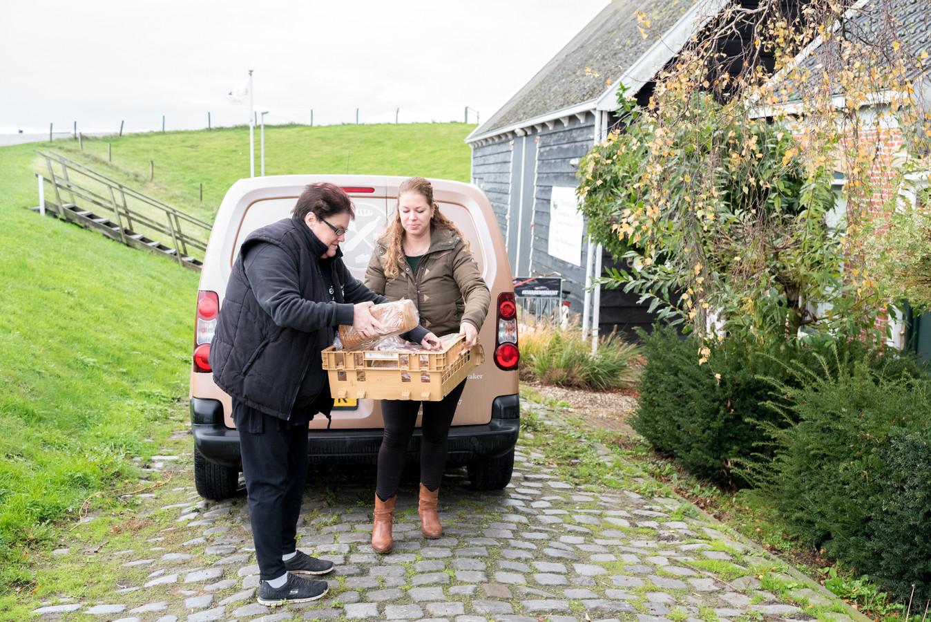 Esther Remeeus levert de eerste vracht bestellingen af bij Sandra de Jonge (links) van 't Spulletje. Het fietscafé is samen met bakkerij De Smaakkraker uit Rilland een afhaalpunt op Waarde begonnen.