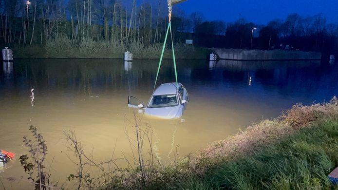 De Volvo V60 wordt uit het water van het kanaal in Moen getakeld.