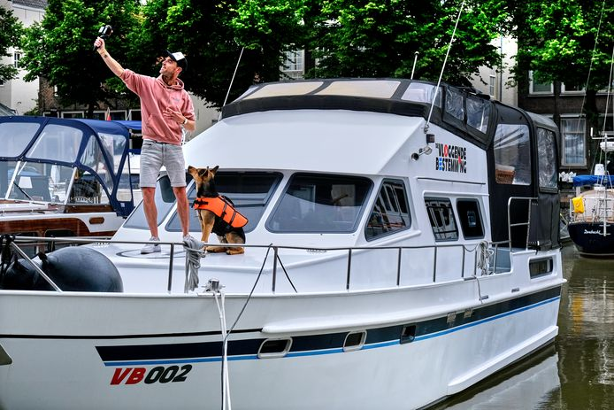 Kees Aantjes met hond Chiko op zijn boot.