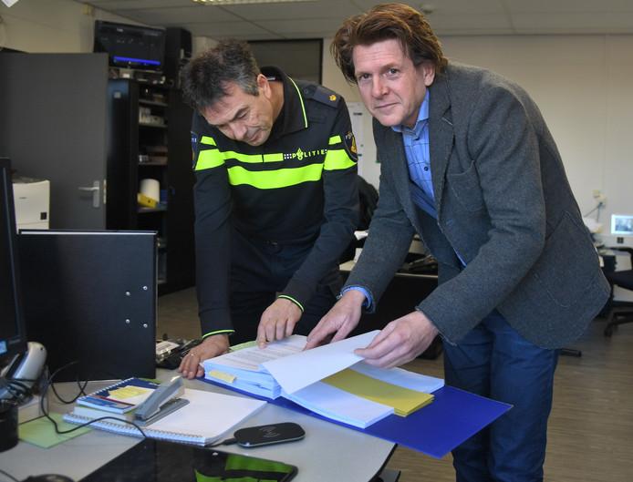 Aris van Herwijnen (rechts) bekijkt met een collega het dossier.