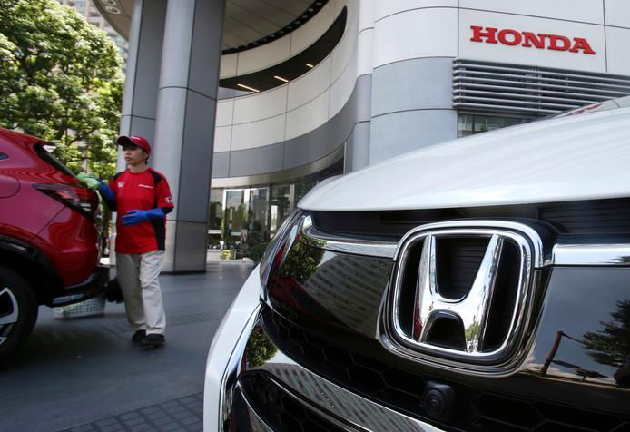 Een personeelslid van Honda poetst auto's bij het hoofdkantoor van de autofabrikant in Tokio.
