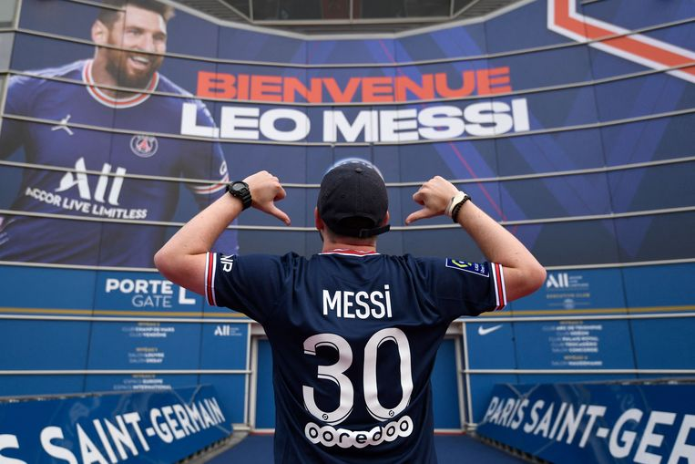 A man poses wearing a jersey of PSG's Argentinian forward Lionel Messi in front of a large banner reading 'Welcome Leo Messi' on a wall of the Paris Saint-Germain's (PSG) Parc des Princes stadium in Paris on August 11, 2021. - Determined queues formed before dawn in front of the club boutique and roucous crowds gathered outside the stadium on August 11 as Lionel Messi was officially unveiled as a Paris Saint-Germain player. (Photo by Bertrand GUAY / AFP) Beeld AFP