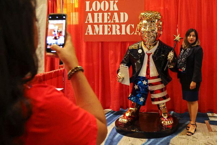 Het gouden beeld van Donald Trump op de 'Conservative Political Action Conference' (CPAC) in Orlando (Florida)  is een publiekstrekker. Iedereen wil met het beeld op de foto. (AP/Sam Thomas/Orlando Sentinel)