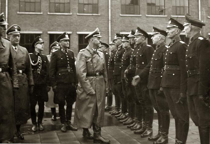 In gezelschap van SS-er Hanns Albin Rauter (geheel links) en Rijkscommissaris Arthur Seyss-Inquart (links) inspecteertde hoogste SS-baas Heinrich Himmler in 1944 het opleidingsbataljonvan de politie te Schalkhaar.
