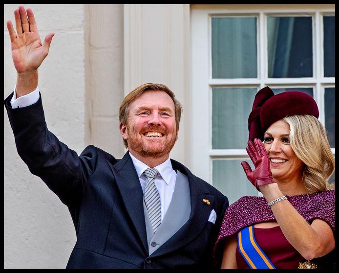 Koning Willem-Alexander met baard zwaait naar het volk met Koningin Maxima aan zijn zijde.