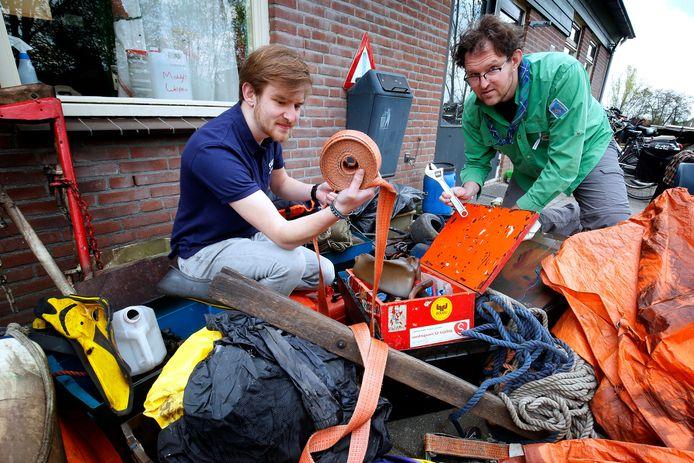 Voorzitter Jordy Dijkshoorn (rechts) en teamleider Sander Vink inspecteren spullen na de brand.