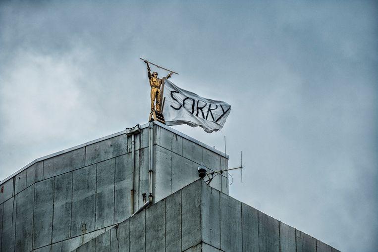 Vorig jaar stelden een aantal kunststudenten uit het conservatorium van Antwerpen 'De man die de wolken meet' in vraag: ze maakten een vlag vast aan het standbeeld met 'sorry' in grote zwarte letters. Beeld Tim Dirven