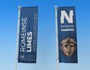 De vlaggen waarmee Berg en Dal (links) en Nijmegen (rechts) de aanwijzing tot werelderfgoed van de limes gaat vieren en uitventen.
