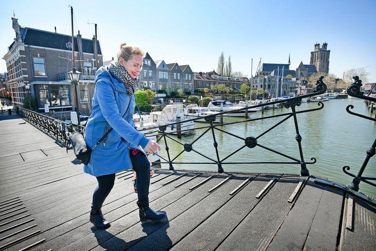 Een vrouw loopt over een van de bruggen in het oude deel van de stad, met op de achtergrond de Grote Kerk.  Beeld null