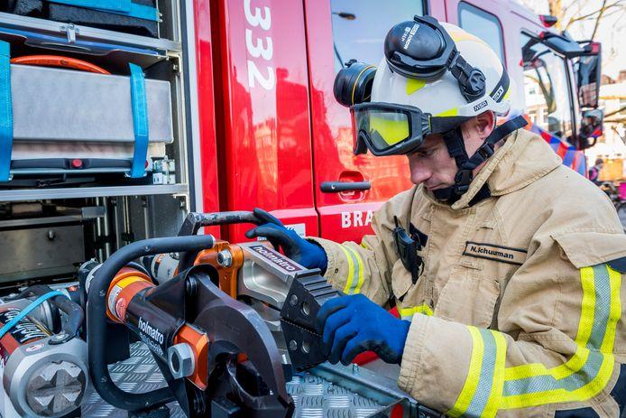 Foto ter illustratie. Een brandweerman pakt knip en breek gereedschap uit de brandweer auto.