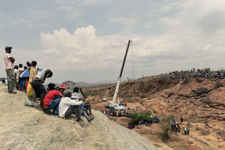 Omstanders kijken naar de reddingswerkers die proberen water uit de schacht te pompen om de mijnwerkers te bereiken. Beeld AFP