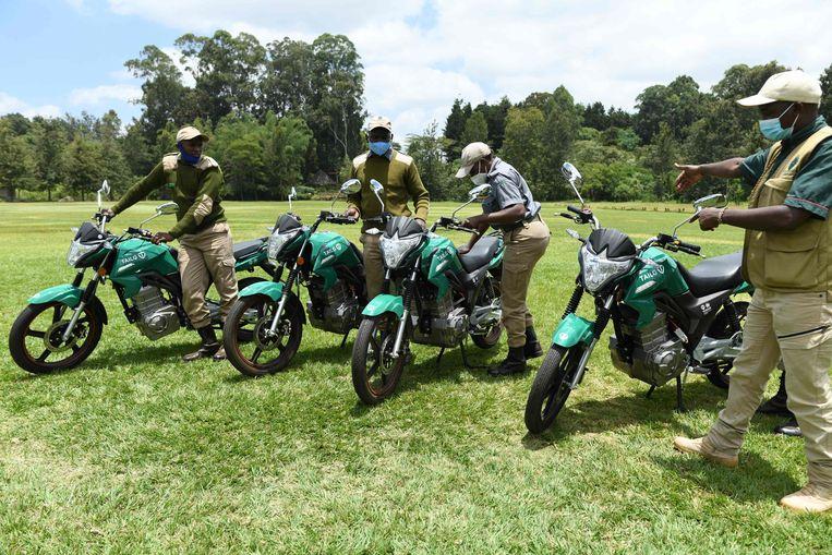 Keniaanse boswachters in het Karura-bos in Nairobi staan naast elektrische motoren die ze  in het kader van het Electric Mobility-programma van de Verenigde Naties gaan gebruiken. De VN willen hiermee stimuleren dat ook armere landen de transitie naar schone vervoermiddelen maken.  Beeld AFP