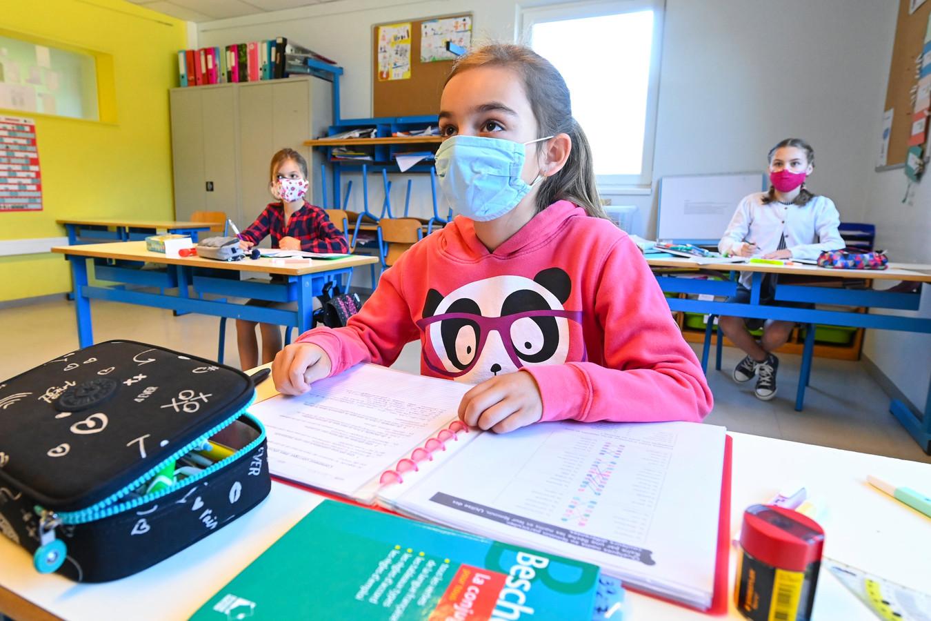 Kinderen met mondkapjes op in de klas.