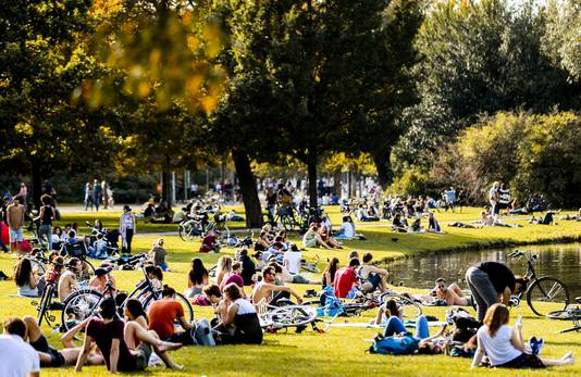 Mensen genieten van het mooie nazomerweer in het centrum van Amsterdam. Zelden was het zo warm in oktober.